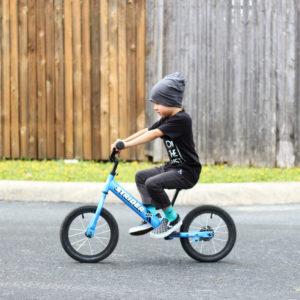 boy on blue bike riding on pavement along a fence