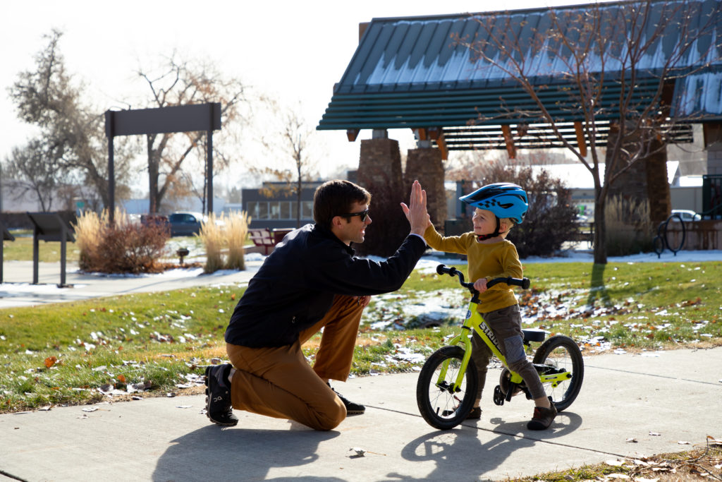 boy on bike giving dad high five