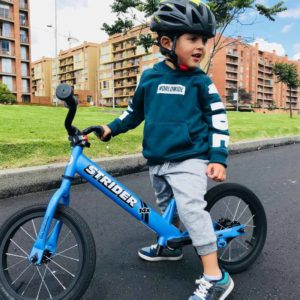 little boy on blue bike on road in front of apartments