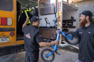 Black Hills Harley-Davidson Employees Load Strider Bikes Into RCAS Bus for Delivery