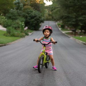 little girl looking surprised while riding a Strider 14x down the street.